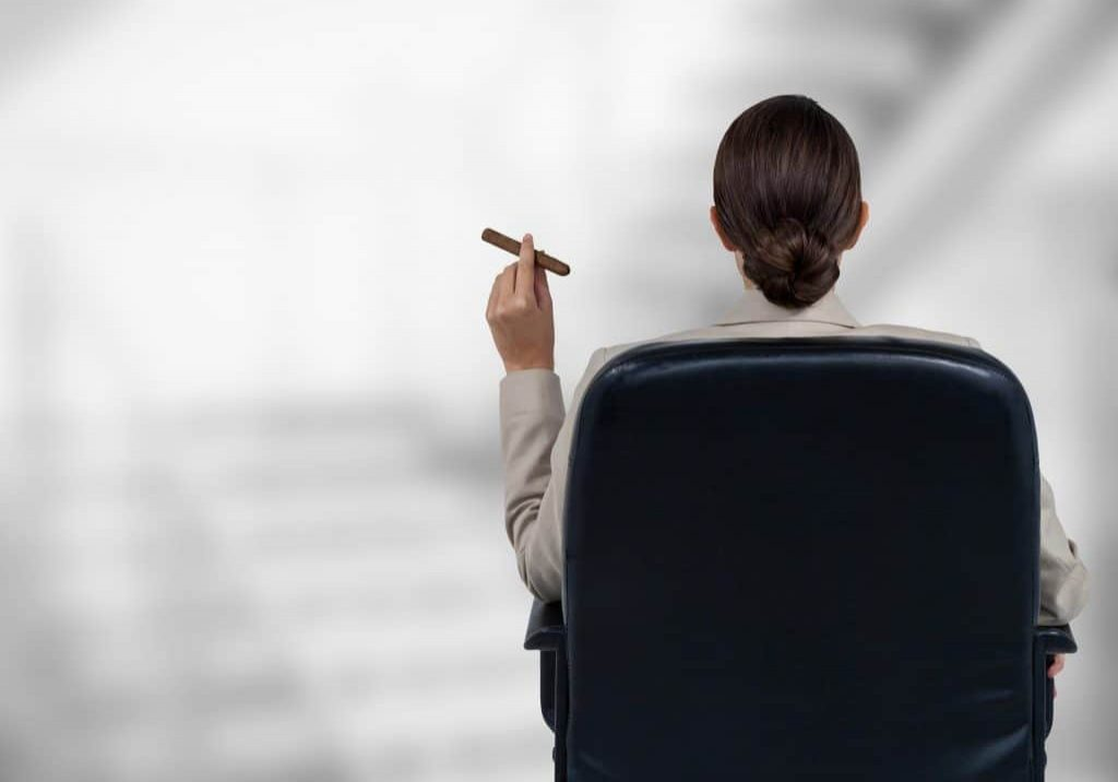Back of seated business woman smoking cigar against blurry grey stairs